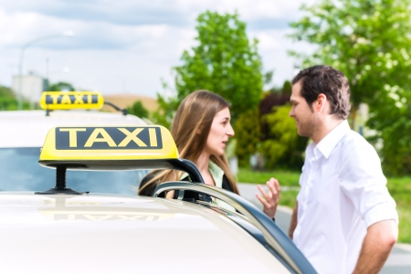 Young woman and driver standing together in front of taxi, she has reached her destination photo