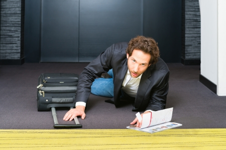 Young man in the hotel corridor is stumbled in hurry along luggage and suitcase, and now lying on the floor Stock Photo