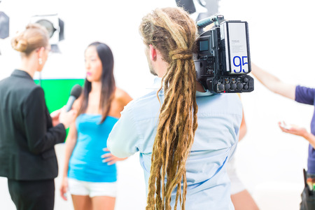 interviewing: Camera man filming on set for video production an interview situation with actress or celebrity  Stock Photo