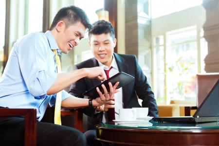 business asia: Due imprenditore o ufficio cinesi asiatici con un incontro di lavoro in una lobby che parlano di documenti su un computer tablet mentre beve il caff�