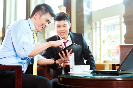 Two Asian Chinese businessman or office people having a business meeting in a hotel lobby discussing documents on a tablet computer while drinking coffee  photo