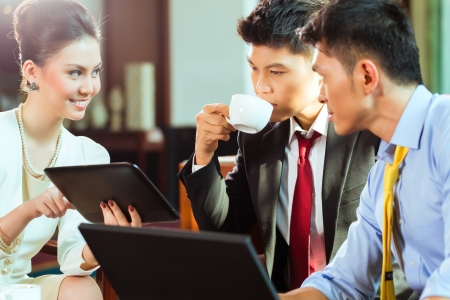 Three Asian Chinese office people or businessmen and businesswoman having a business meeting in a hotel lobby discussing documents on a tablet computer while drinking coffee  Imagens