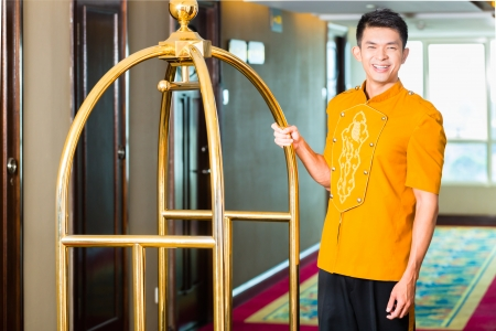 Asian Chinese baggage porter or bell boy or page bringing the suitcase of guests with a box van to the hotel room  photo