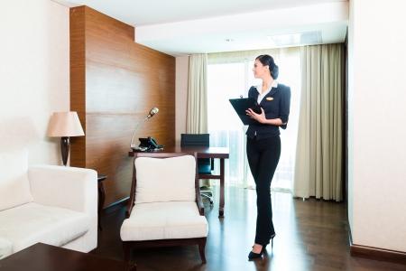 orden y limpieza: Director de la limpieza asi�tica china o el asistente de control o de control de la sala o el traje de un hotel con una lista de verificaci�n en la pulcritud Foto de archivo