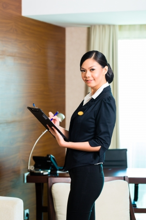 tidiness: Asian Chinese Housekeeping manager or assistant controlling or checking the room or suit of a hotel with a checklist on tidiness  Stock Photo