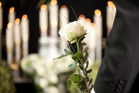 arreglo floral: La religi�n, la muerte y dolor - hombre en el funeral con la rosa blanca de luto por los muertos Foto de archivo