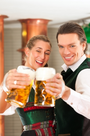 Man and woman with beer glasses in Bavarian tracht in brewery in front of a brew kettle Stock Photo - 25186672
