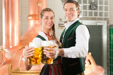 tracht: Man and woman with beer glasses in Bavarian tracht in brewery in front of a brew kettle
