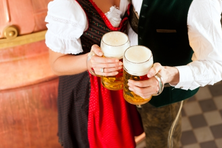 Man and woman with beer glass in brewery photo