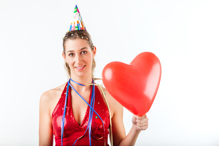 Woman celebrating birthday or valentines day holding heart balloon with party hat photo