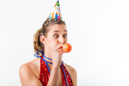 Woman celebrating birthday blowing up balloon, isolated shot photo