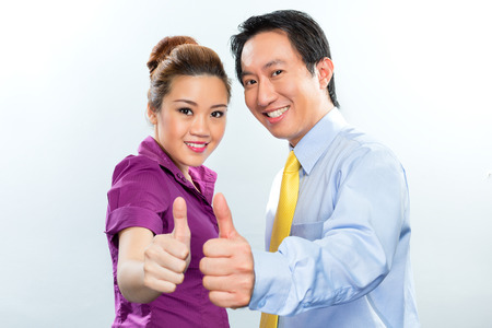 Motivated Asian business employees or colleagues giving thumbs up for optimistic atmosphere Stock Photo
