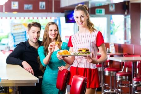 comida rápida: Los amigos o pareja comiendo comida r�pida en Am�rica del restaurante de comida r�pida, la camarera que llevaba un traje corto Foto de archivo