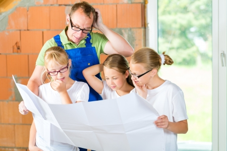 homeowners: Father and kids or daughters and friends looking at a construction plan on a building site Stock Photo