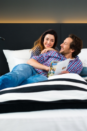 kingsize: Young Couple lying in the bed of a hotel room, they are on vacation and using the wi-fi in the room for internet with the computer