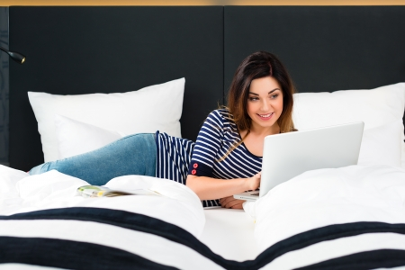 Young woman sitting on bed of a hotel room, she is on vacation and using the wifi in the room for internet with the computer photo