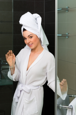 Young woman in the hotel bathroom, she comes freshly showered from the shower stall photo