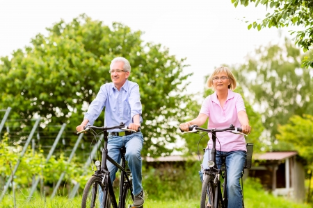 Senior Man and woman exercising with bicycles outdoors, they are a couple photo