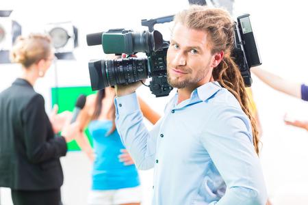 hombre disparando: Hombre de la cámara de filmación en el set de producción de vídeo de una situación de la entrevista con la actriz o una celebridad