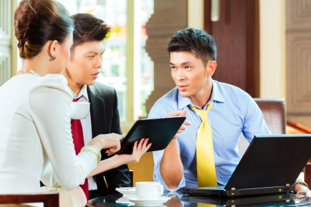 Three Asian Chinese office people or businessmen and businesswoman having a business meeting in a hotel lobby discussing documents on a tablet computer while drinking coffee  photo