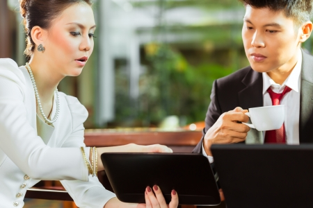 Two Asian Chinese office people or businessman and businesswoman having a business meeting in a hotel lobby discussing documents on a tablet computer while drinking coffee  photo