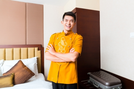 Asian Chinese baggage porter or bell boy or page bringing the suitcase of guests to the luxury hotel room  photo
