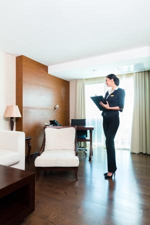 supervisores: Director de la limpieza asiática china o el asistente de control o de control de la sala o el traje de un hotel con una lista de verificación en la pulcritud Foto de archivo