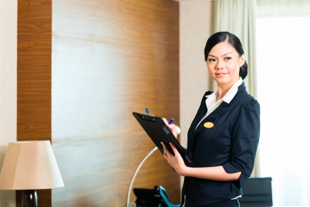 Asian Chinese Housekeeping manager or assistant controlling or checking the room or suit of a hotel with a checklist on tidiness  photo
