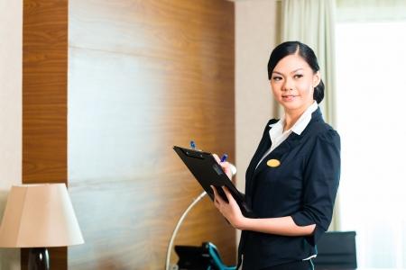 supervisores: Director de la limpieza asi�tica china o el asistente de control o de control de la sala o el traje de un hotel con una lista de verificaci�n en la pulcritud Foto de archivo