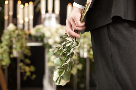 dolor: Religion, death and dolor  - man at funeral with white rose mourning the dead