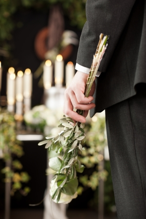 funeral parlor: Religion, death and dolor  - man at funeral with white rose mourning the dead