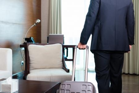 체크인 자신의 트롤리 후 호텔 룸이나 스위트 룸에 도착 출장 관리자 또는 사업가