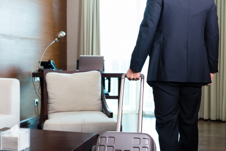 suite: Manager or businessman on a business trip arriving to hotel room or suite after check-in with his trolley