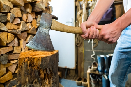 shack: Young man chops firewood or wood with a hatchet or an axe in a shack in the mountains
