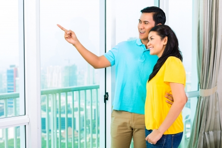 Young Asian handsome couple looking out of the window
