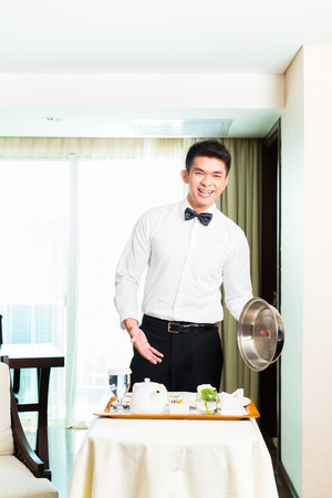 Asian Chinese room service waiter or steward serving guests\ food in a grand or luxury hotel room