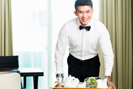 serving food: Asian Chinese room service waiter or steward serving guests food in a grand or luxury hotel room