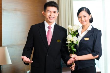 Hotel Manager of directeur als begeleider welkom aankomen VIP-gasten met rozen bij aankomst in luxe of grand hotel