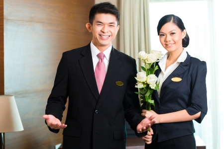 hospitality: Hotel Manager or director and supervisor welcome arriving VIP guests with roses on arrival in luxury or grand hotel Stock Photo