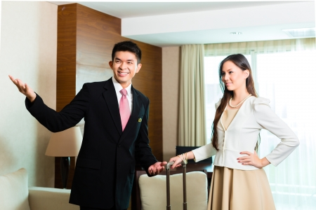 man in suite: Asian Chinese Hotel Manager or director or supervisor presenting arriving VIP guests the room or suite