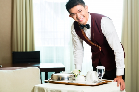 luxury hotel room: Asian Chinese room service waiter or steward serving guests food in a grand or luxury hotel room