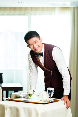 Asiatische chinesische Zimmerservice Kellner oder Steward Bedienung der Gäste Essen in einem großen oder Luxus-Hotelzimmer