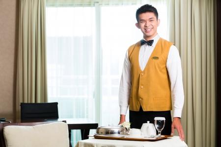 Asiatische chinesische Zimmerservice Kellner oder Steward Bedienung der Gäste in einem großen Lebensmittel-oder Luxus-Hotelzimmer