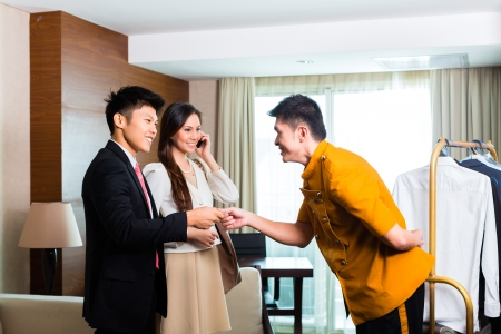 porter: Baggage porter or bellboy or page receiving tip for delivering the suitcase of guests to the hotel room or suite