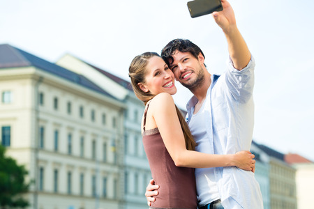 Man and woman or young couple making trip as tourists in Munich and making snapshot with the smartphone or phone photo