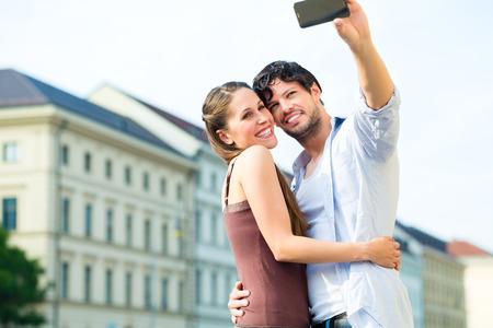 Man en vrouw of jonge paar making reis als toeristen in München en het maken van snapshot met de smartphone of telefoon