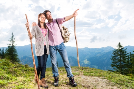 Hiking - Young couple standing on mountain summit in the Bavarian Alps enjoying the panorama in their leisure time or vacation photo