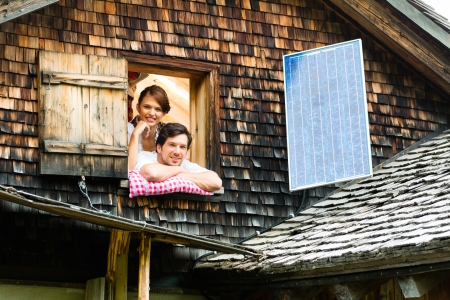 trachten: Young couple in bed on the floor of a barn or a mountain hut in the Alps enjoys the leisure time