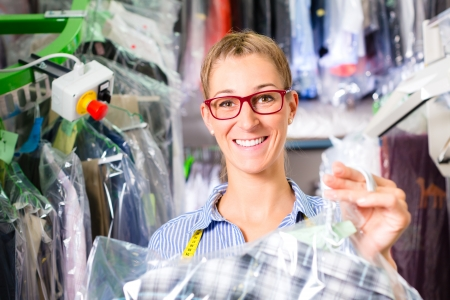 drycleaning: Female cleaner in laundry shop or textile dry-cleaning next to clean clothes in garment bags