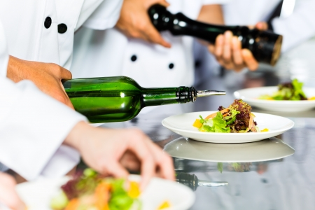 aceite de cocina: Cocinero indonesia asi�tica junto con otros cocineros en el restaurante o en un hotel comercial de cocci�n de la cocina, terminando plato o plato
